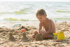 The child sits on the sandy beach of the reservoir and enthusiasm molds of sa Stock Photos
