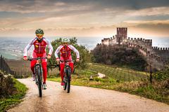 Cyclists train on the hills surrounding the castle of Soave. Stock Photos