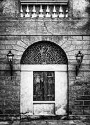 Facade of an ancient Italian villa with artistic iron grill. Stock Photos