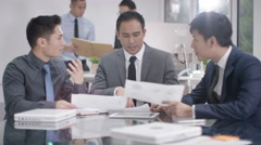 4K Corporate business group in a meeting with close up handshake in foreground - stock footage