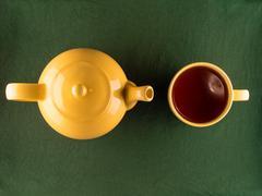 Yellow teapot and mug with tea, copy space - stock photo