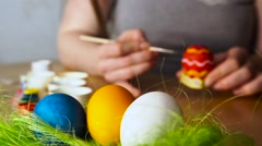 A young Woman Paints Easter Egg with a Brush on the background of Wooden Table Stock Footage