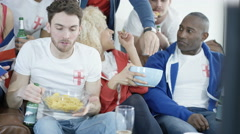 4K Friends hanging out to watch sports game on TV, drinking beer & eating snacks Stock Footage