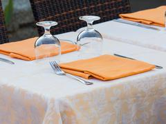 restaurant table prepared with damask  table cloth orange napkin - stock photo