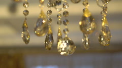 Moving of a bright crystal chandelier on a dark background. Slowly - stock footage