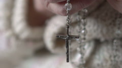 Closeup crucifix and crystal rosary in old hands. Slow motion - stock footage