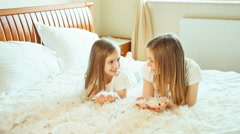 Cute girls lying on the bed and playing with fluff and feathers - stock footage