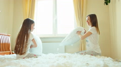 Mother and daughter fighting pillows on the bed in sunny bedroom in fluff - stock footage