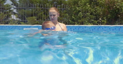 Mother Teaching Son Swimming Stock Footage