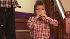 Standing black kid plays flute. Stock Footage