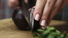 Female hands cutting red onion into rings at the table, on kitchen background Stock Footage