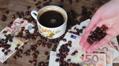 Coffee Beans, Coffee Cup and Euro on a Wooden Table Stock Footage