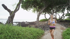 Running woman runner on trail by beach in summer - sport girl jogging - stock footage