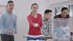 4K Casual office workers aiming rolled up papers for waste paper basket - stock footage