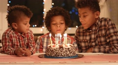 Boy blows out the candles and make a wish. Stock Footage