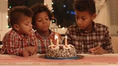 Kids lighting birthday cake's candles. - stock footage