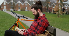4k, A young man reading an enjoyable book in the park. Stock Footage