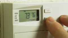 Man adjusting the thermostat to save energy 4k Stock Footage