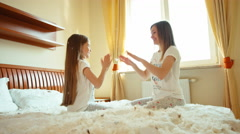 Happy daughter and mother sitting on the bed and playing in Okay play - stock footage