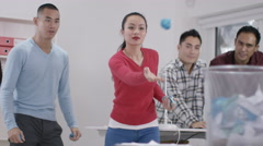 4K Casual office workers aiming rolled up papers for waste paper basket Stock Footage
