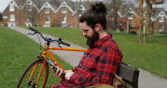 4k, A young man using his tablet while taking a break in the city with his bicyc Stock Footage