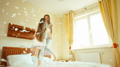 Happy family jumping and spinning on the bed. Among the fluff and feathers - stock footage