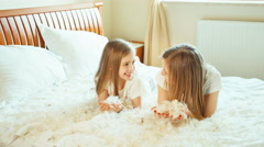 Happy cute girls lying on the bed and playing with fluff and feathers - stock footage