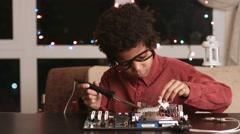 Darkskinned boy solders motherboard. Stock Footage