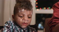 Untidy boy smeared in cake. - stock footage