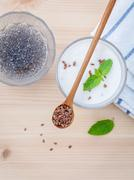 Nutritious flax seeds with glass of greek yogurt and wooden spoon for diet  m Stock Photos