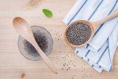 Nutritious chia seeds in glass bowl with wooden spoon for diet food ingredien Stock Photos