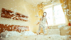 Girl jumping and spinning on the bed. Among the fluff and feathers - stock footage