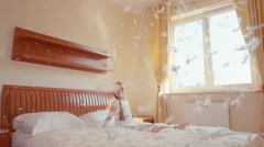 Girl 7 years old lying on the bed and playing with fluff and feathers Stock Footage