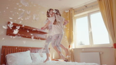 Happy daughter and mother jumping and spinning on the bed. Among the fluff - stock footage