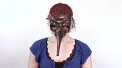 Portrait of a young red headed woman with a long nose masquerade mask on (2) - stock footage