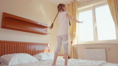 Girl jumping and spinning on the bed. Among the fluff and feathers. Slomotion - stock footage