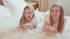 Cute happy girls playing with fluff and feathers in the bed. Slowmotion - stock footage