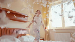 Happy girl jumping and spinning on the bed. Among the fluff and feathers - stock footage