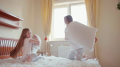 Fighting pillows on the bed. Mother and daughter fighting on the bed - stock footage