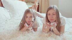 Cute happy girls playing with fluff and feathers. Slowmotion - stock footage