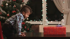 Boy unwrapping gift on table. Stock Footage