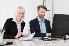 Two Businesspeople Using Computer For Analyzing Graph - stock photo