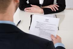Close-up Of Young Businessman Holding Resume At Office Desk - stock photo