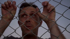 Male Struggling Behind a Wire Fence - stock footage