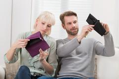 Unhappy Couple Sitting On Sofa Looking At Empty Wallet Stock Photos
