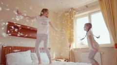Happy family daughter and mother jumping and spinning on the bed in fluff - stock footage