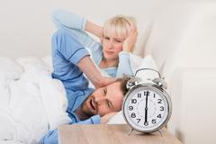 Exhausted Young Couple Awakened By Alarm Clock In Bedroom At Home Stock Photos