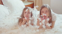 Cute girls lying on the bed and playing with fluff and feathers. Slowmotion - stock footage