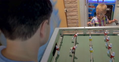 Father and Son Playing Foosball in Arcade - stock footage