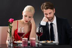 Portrait Of A Sad Couple Having Dinner At A Restaurant With Black Background Stock Photos